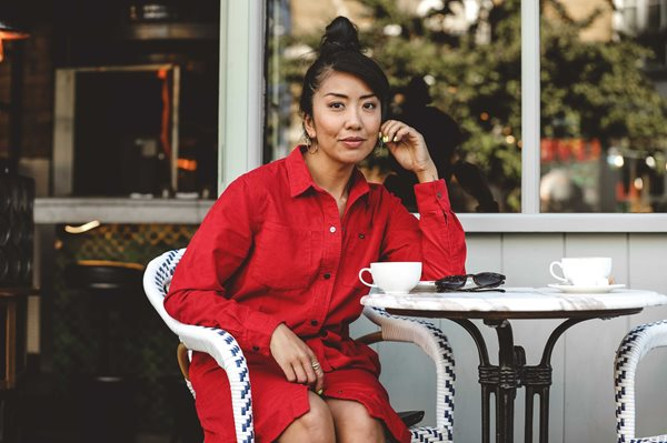 Celeste Wong sitting at a cafe table with a coffee wearing a red outfit.