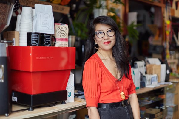 Celeste Wong in a cafe, in front of a La Marzocco espresso machine and coffee merchandise, wearing glasses and a red shirt.